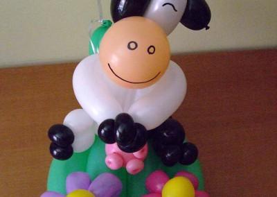 Vaquita con flores y globo flotante.