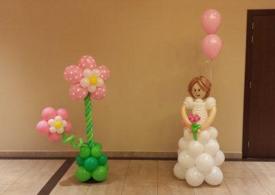 Columna floral y niña de comunión.